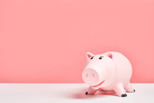 Cute pink piggy bank against the pink colored background