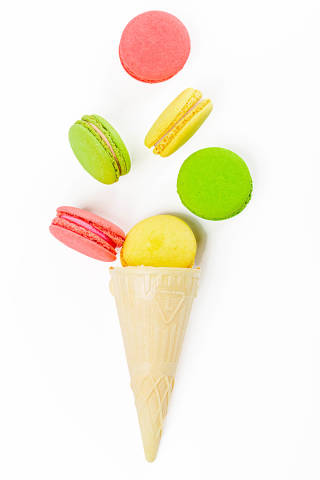 Macaroon on white background, sweet and colorful dessert with waffle cone, top view