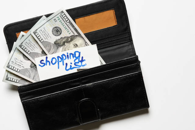 Wallet with money and shopping list