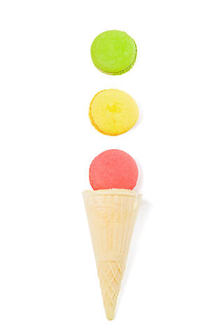 Pink, yellow and green macaroons on white background with waffle cone