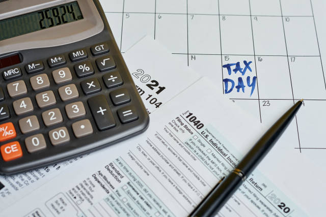 Business concept - tax form with pen and calculator on the calendar
