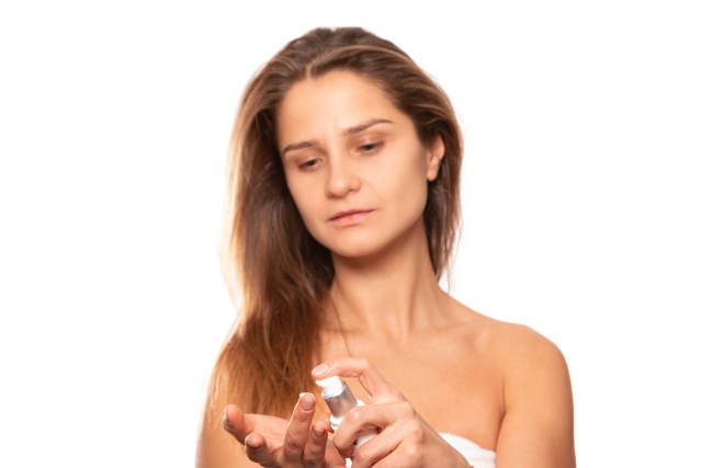 Woman applying cream to her hand
