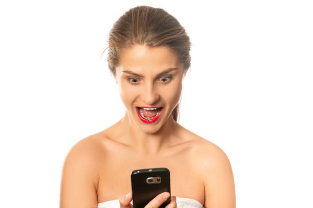 Shocked surprised girl looking at mobile phone with open mouth