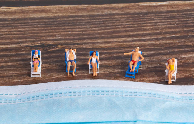 Miniature people relaxing near the face mask