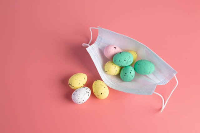 Medical face mask and colorful easter eggs