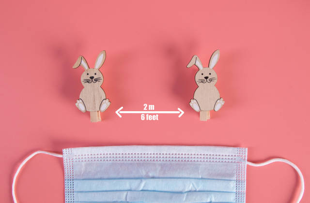 Social distancing concept with cute Easter bunnies and medical face mask