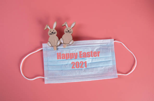 Easter bunnies with medical face mask and Happy Easter 2021 text