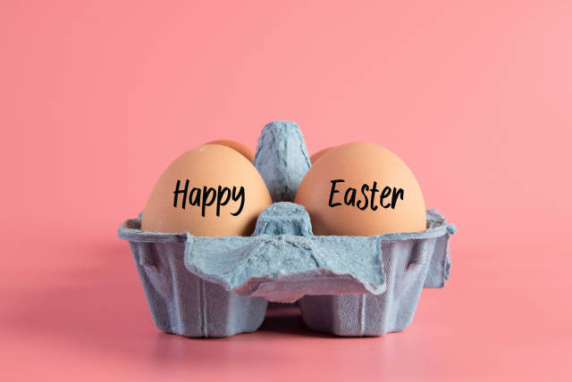 Raw brown eggs in egg box with Happy Easter text