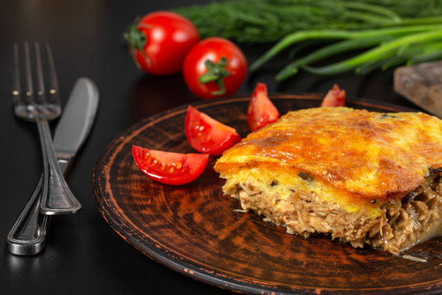 Piece delicious tart with chicken, mushrooms and cheese on plate