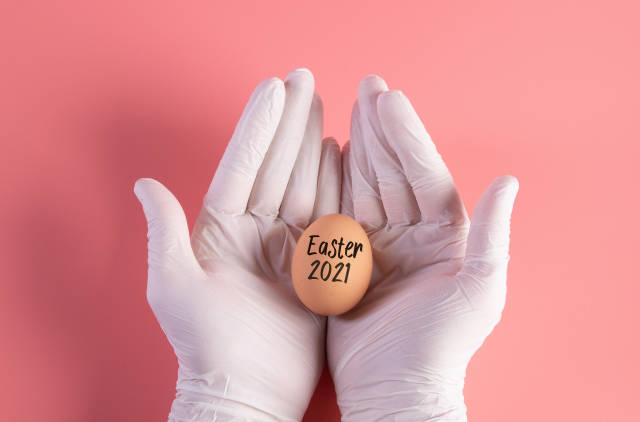 Hand in white protective gloves holding egg with Easter 2021 text