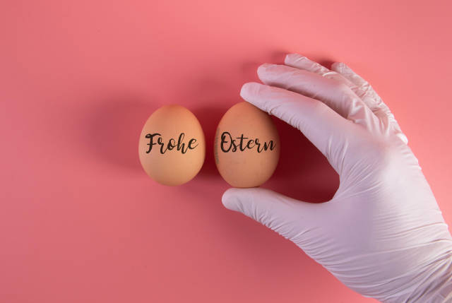 Hand in protective gloves with two eggs and Frohe Ostern text