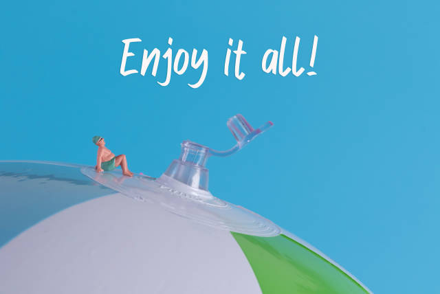 Miniature man in swimsuit sitting on a beach ball with Enjoy it all text