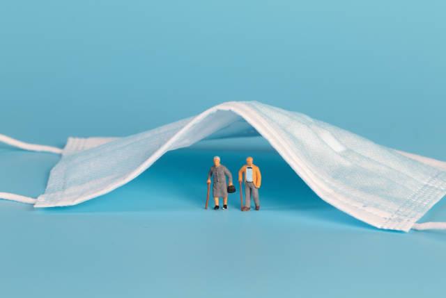 Older couple standing under medical face mask