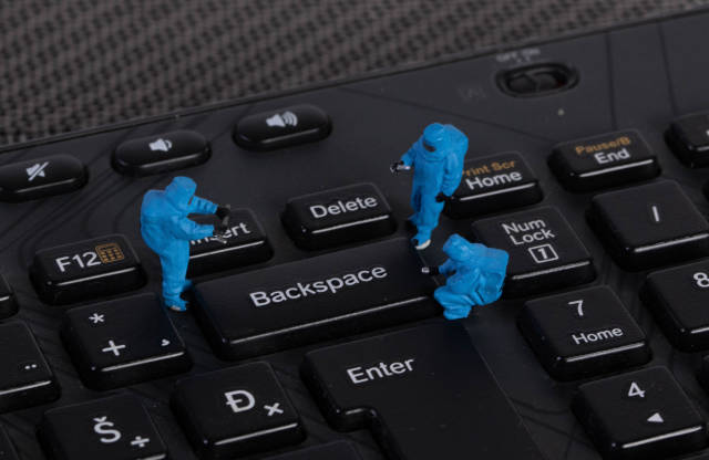 Miniature workers in protective clothes on a keyboard with Backspace button