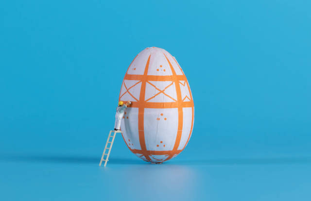 Miniature painter painting easter egg on blue background