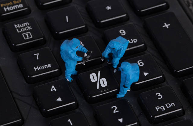 Miniature workers in protective clothes on a keyboard with Percentage button