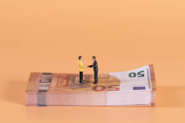 Two miniature businessman shaking hands on a stack of Euro money