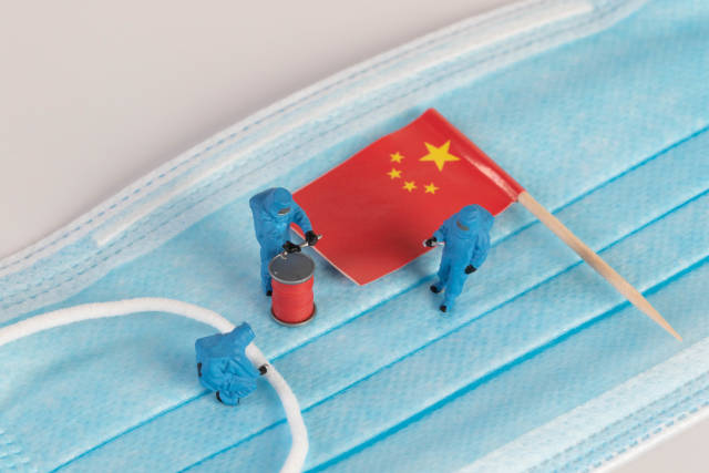 Miniature workers in protective clothes on a medical mask with flag of China