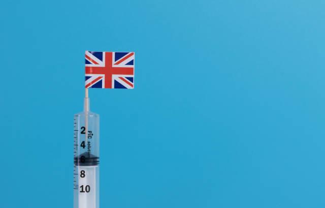 Syringe with flag of UK on blue background