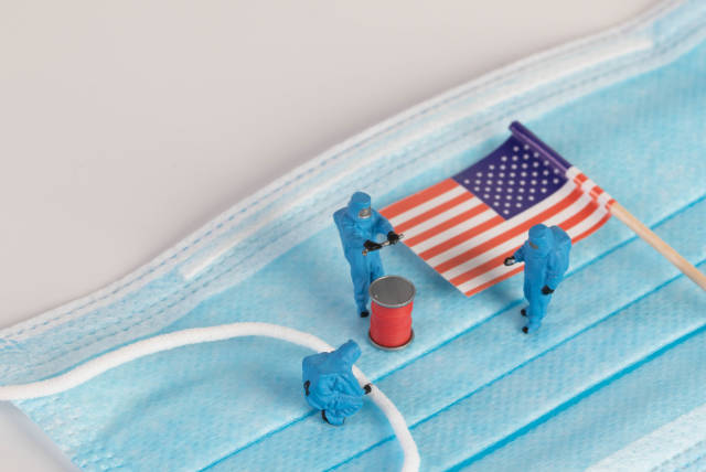 Miniature workers in protective clothes on a medical mask with flag of Unites States of America