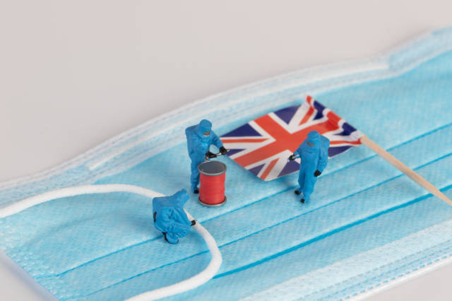 Miniature workers in protective clothes on a medical mask with flag of United Kingdom