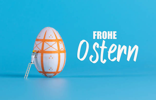 Miniature painter painting easter egg and Frohe Ostern text