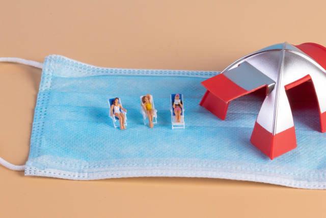 Group of miniature people sunbathing in deckchairs with face mask and camping tent