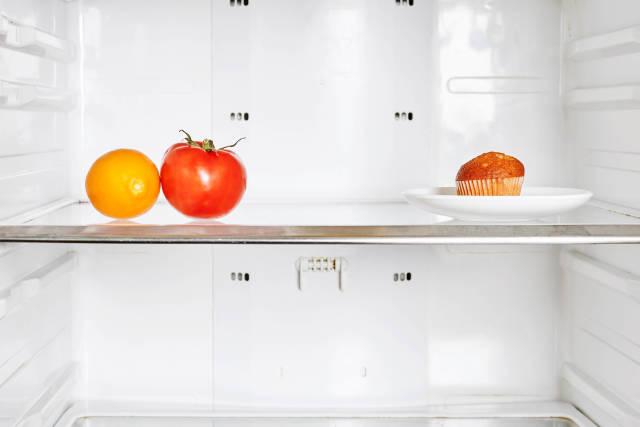 Tomato, lemon fruit and a cake in the fridge