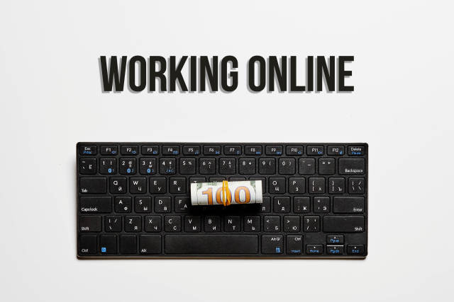 Working online concept with pc keyboard and us dollar bill