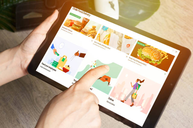 A person ordering food delivery on the tablet