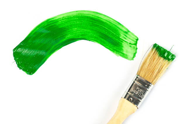 Paint brush with wooden handle and dab of green paint