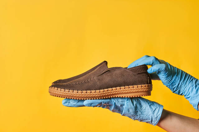 Woman in medical gloves holds a trendy leather shoe