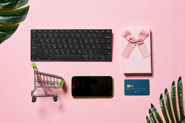 Shopping cart, credit card, mobile phone, gift box and computer keyboard on the pink background