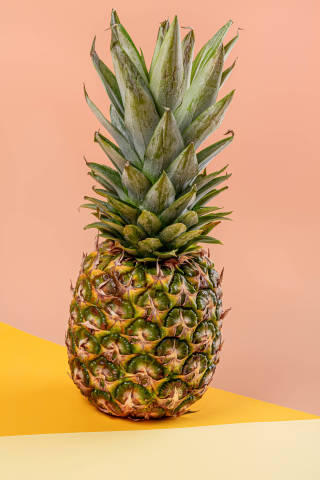 Ripe whole pineapple on yellow orange background