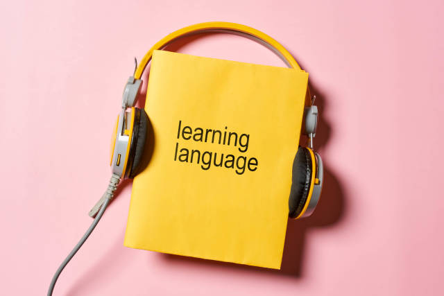 Learning a foreign language - headphones and book