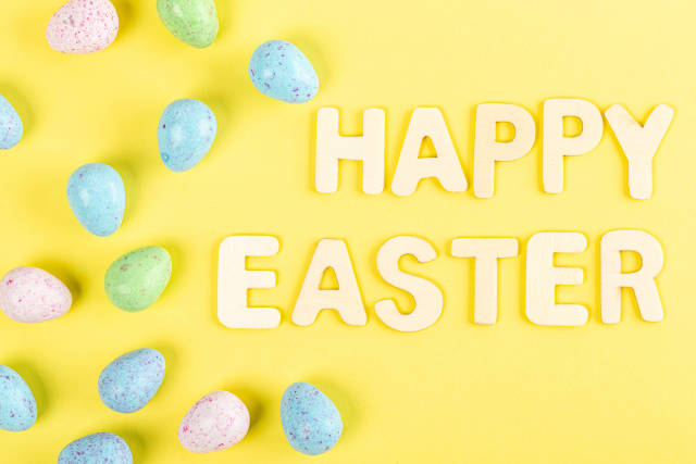 Happy easter text with chocolate eggs on yellow background