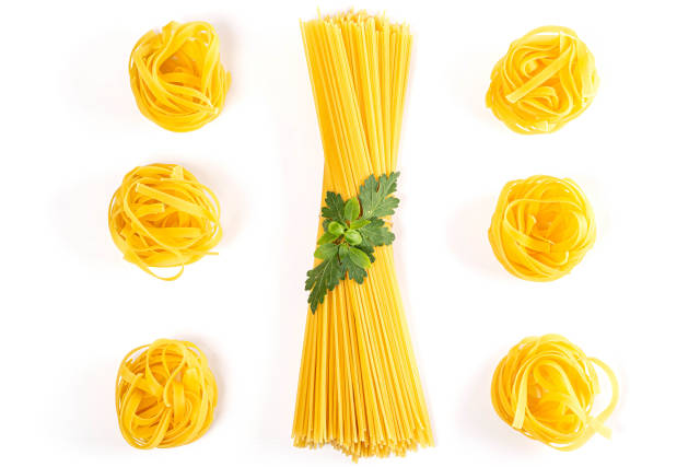 Fresh uncooked fettuccine pasta and spaghetti with with basil and parsley on a white background