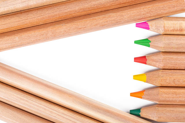 Multicolored pencils background with white free triangle