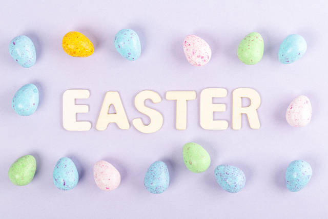 Frame of multicolored chocolate eggs on a purple background with the inscription easter from wooden letters