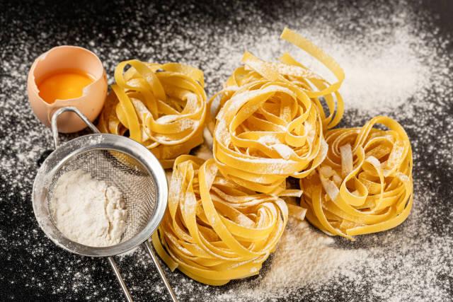 Fettuccine italian pasta on a black background with sprinkled flour