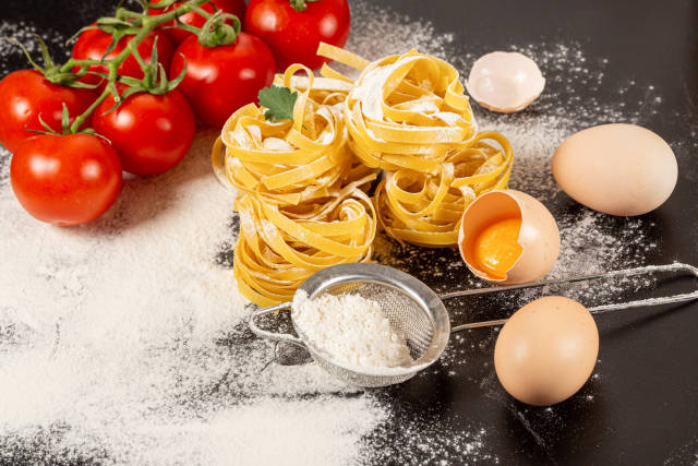Uncooked rolled traditional italian pasta on dark background with tomatoes, eggs and flour