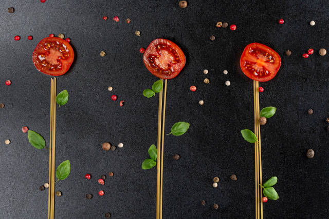 Flowers made from raw spaghetti, tomatoes and basil leaves on black background