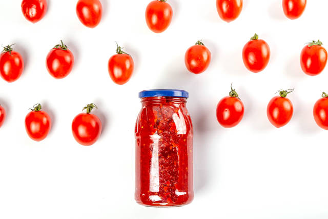 Glass jar with tomato sauce and fresh tomatoes on a white background