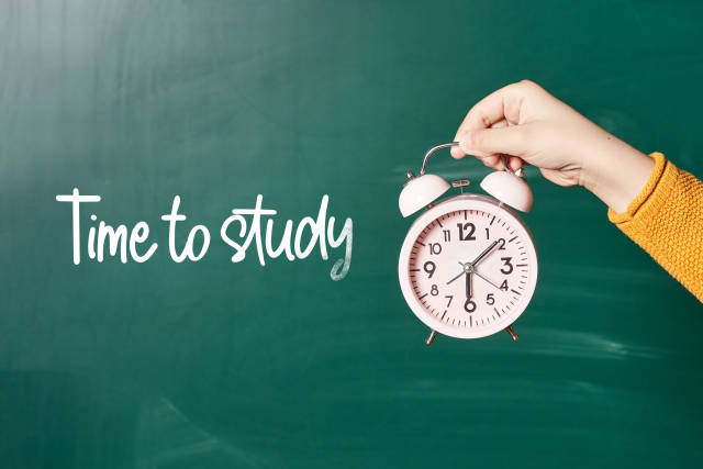 Time to study text on chalkboard and hand holding alarm clock