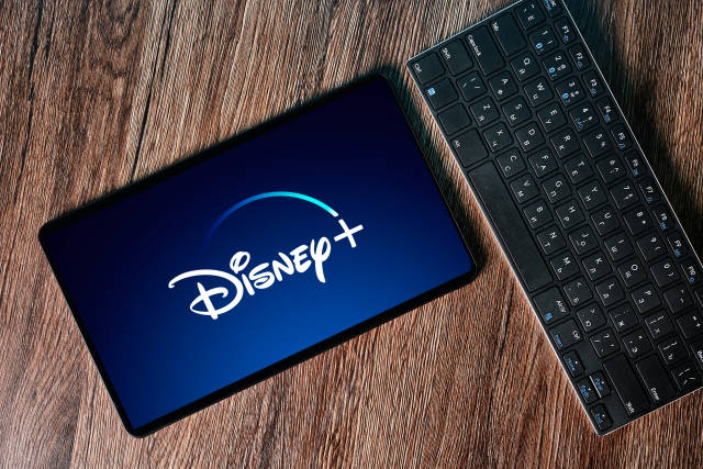 Computer keyboard and tablet with Disney+ logotype on display