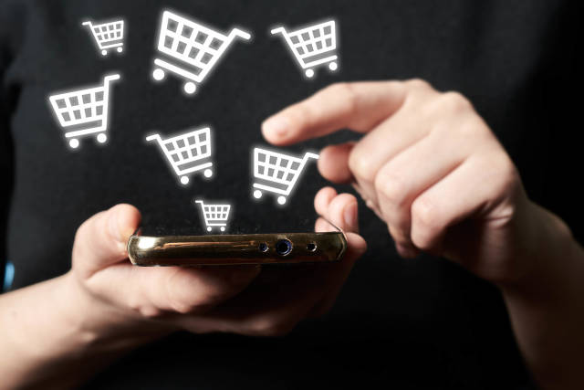Online shopping and payment - man using smartphone with shopping cart icons