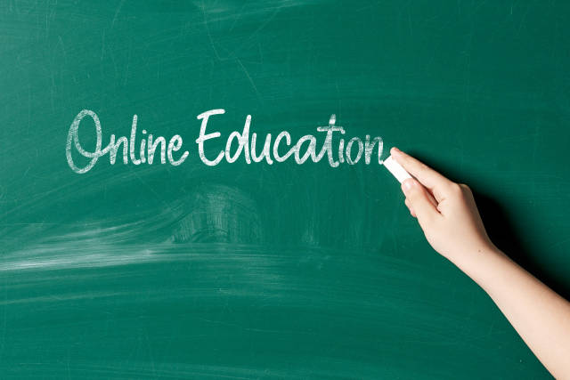 Hand of a woman writing on the chalkboard - online education