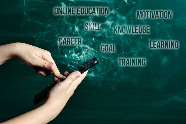 Hand holds smartphone near chalkboard with text clouds - online education, motivation, skill, career, goal, knowledge, learning, training, goal,