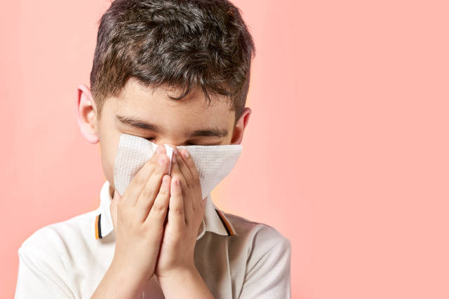 Boy with a tissue blowing his nose