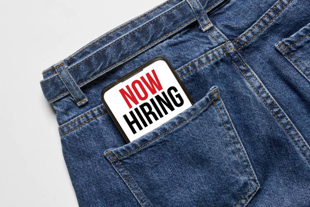 Now hiring phrase on mobile phone screen in the pocket of jeans